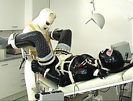 After the first examination and some more rubber bag breathing, now the whole of the sweet black and white rubberdolly Uschi is started to be examined and dilated with the Rubberfingers of the white r...